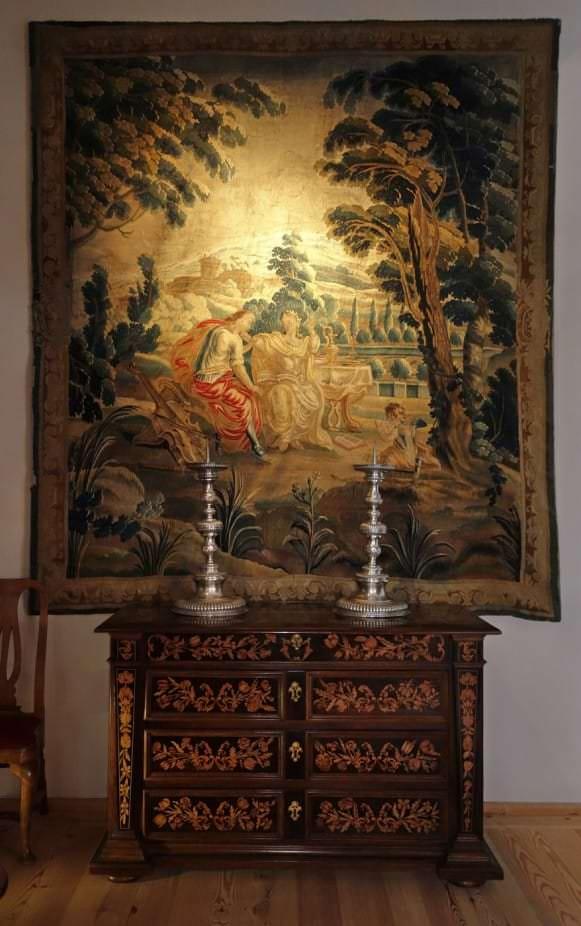 """Gobelēns """"Apollons un Kalliope"""" (Beļģija, Brisele, 18. gs. 1. puse), kumode-sekretārs ar intarsijām (Holande, 17. gs. beigas) un svečturi (Kurzeme, Liepāja, Johans Lautenzaks, 1716)"""